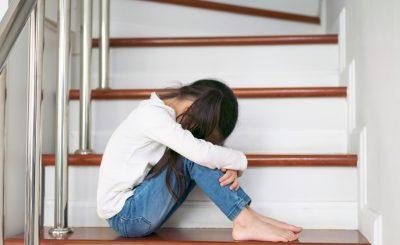 Une enfant recroquevillée dans les escaliers