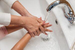 Une femme qui se lave les mains avec son enfant