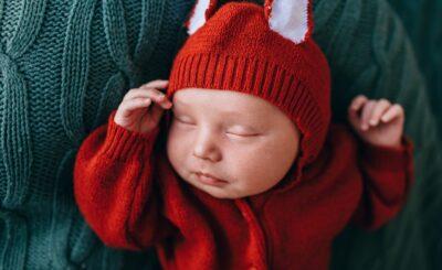 bébé dans barboteuse renard orange sur plaid vert